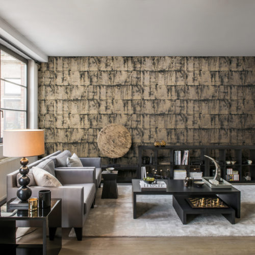 Contemporary living room. On the far wall: grey and gold Antarès by Omexco wallcovering. Standing lamp and black coffee tables.
