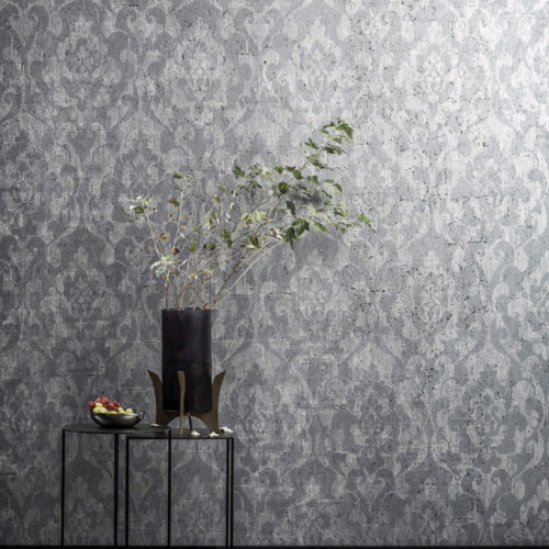 Wall with ANT404 Omexco wallcovering, black vase with branch on a table. There's fruit on the table. In front of the table is a soft grey carpet.