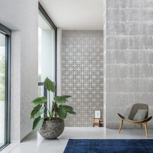 Well lit room with 3 walls of cork wallcovering. One with silver blocks, one with a silver geometrical design and one plain with golden dots. Armchair and large plant, bleu carpet.