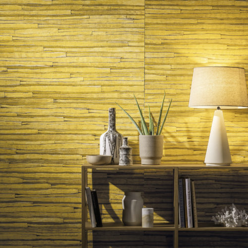 Close up of yellow waterlily wallcovering with wooden shelves. White lamp, books and a sea fossil.