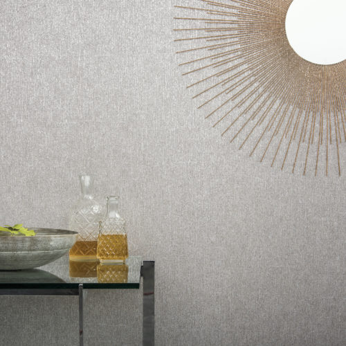 Detail of a plain Bijou wallcovering. Sun shaped mirror. Glass table with two glass carafes. Bowl with leaves.