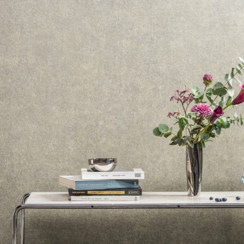 Decor with Bijou plain wallcovering. Metal table, vase with pink flowers. Glass bowl with blueberries.