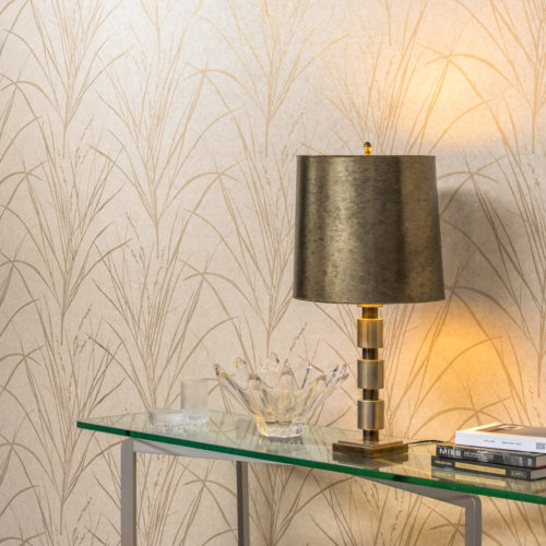 Detail of Bijou wallcovering with golden plant leaves. Glass table, brass lamp.