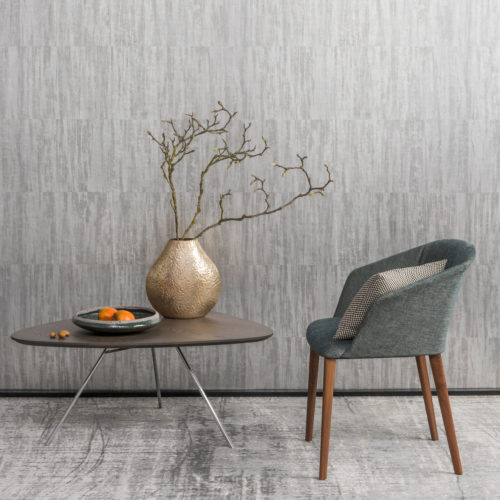 Fresh decor with metallic wallcovering from the Bijou range. Tripod leg table. Golden vase with branches. Bowl with persimmon fruit.