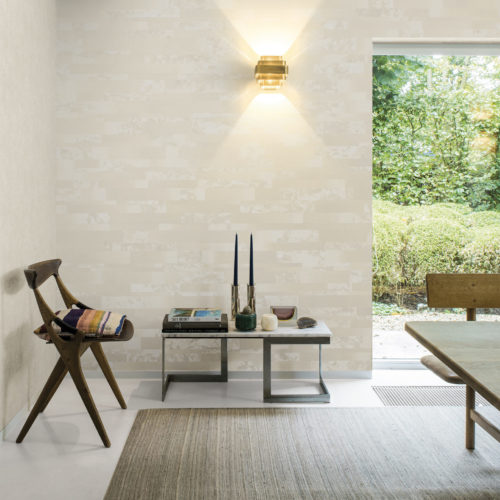 Bright room with wooden dining table. Old chair with pillow. Golden lamp shining on beige and white paper collage Bijou wallcovering. The marble in the wallcovering is also in the coffee table.