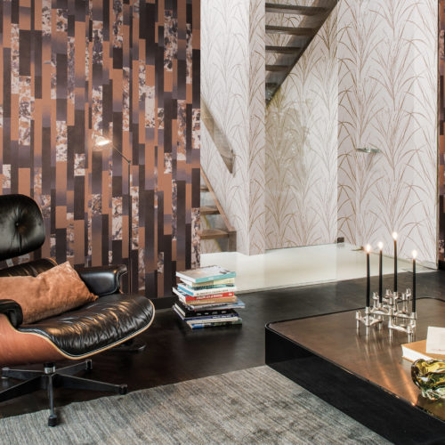 Tactile room with black floor. Stunning Vitra Eames lounge chair. It goes well with the copper and marble Bijou wallcovering. Bright staircase in the middle. Golden leaf Bijou wallcovering.