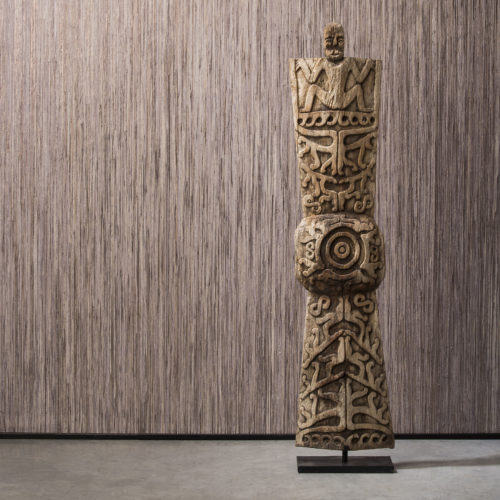 Detail of Borneo raffia wallcovering with wooden totem. The wallcovering is installed vertically.
