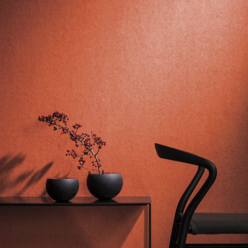 Vibrant orange wallcovering in contrast with a black chair and two dark, round vases on a metal console. Branch with berries.