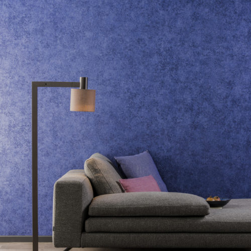Taupe chaise longe and reading light with square corners. They stand in front of bright blue non-woven wallcovering from Omexco Collages.