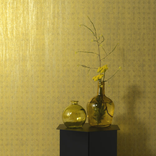 In this picture we show one of the wallcoverings in the Elixir range. Small circles, infinitely repeated, form the decor to two amber coloured vases with yellow flowers.
