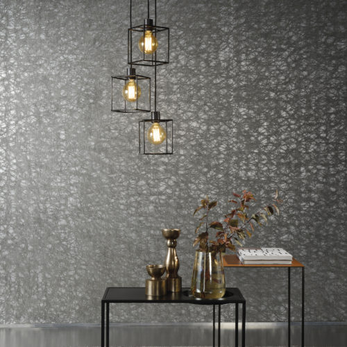 Give you interior something exclusive with this swirling lacework from the Omexco Elixir collection. Combined here with two metal tables, one black, one copper. The metal wire lamps make the satin silver foil and dark grey lacework shimmer.