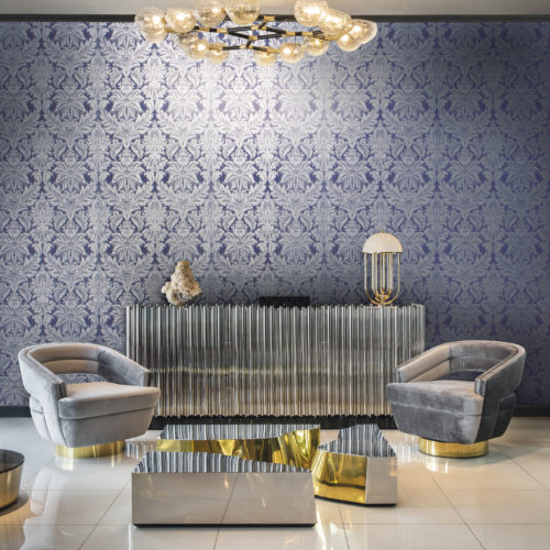 Room with a lot of silver and gold details. Grey velvet chairs, impressive lamps and centre table. The purple damask with silver flowers on the wall goes well with it.