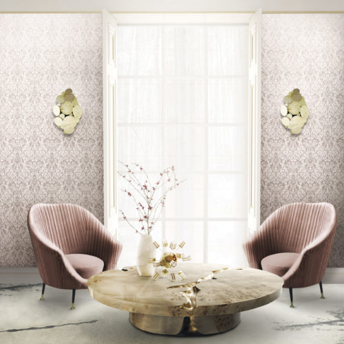 Well lit living room with large window. On both sides of the window pink Gala wallcovering with a foil damask, golden wall lamps. called Newton. Pink velvet chairs by Koket, empire center table.
