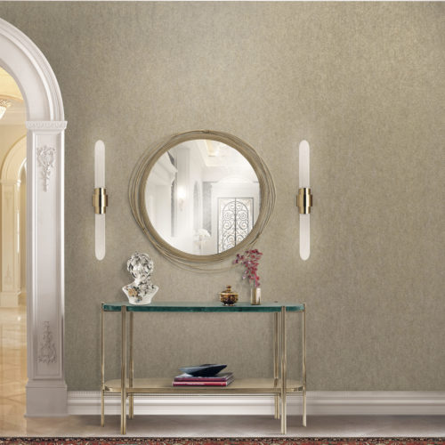 Wall in a hallway with mirror and two lamps on each side of the mirror. The mirror is decorated with cables. Console in glass and gold metal. Buste.