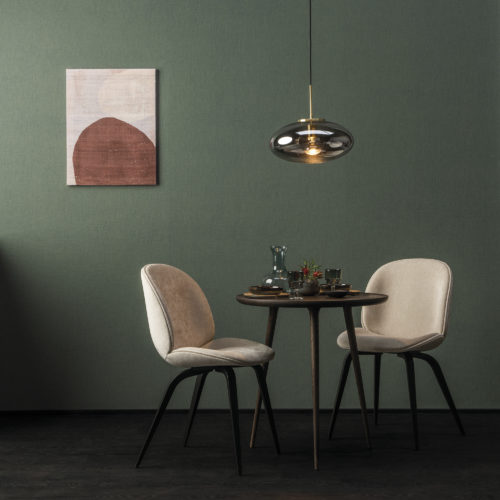 In this picture, we see a small dining table with two white chairs and a glass pendulum lamp. On the walls, Omexco's High Performance Texture wallcoverings are shown. We see the design 'linen' in moss green. It's the design that reminds us most of the local knowhow of working with Belgian linen.