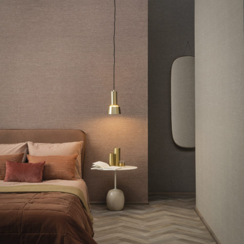 This image shows a hotel room decorated with Omexco's High Performance Textures wallcoverings in light pink and beige shades. The blush coloured pillows on the bed and wooden floor add a touch of warmth to the space.