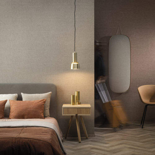 On the walls of this hotel room: the Abaca design in beige and blush hues from Omexco's High Performance Textures collection. It's a semi plain non-woven wallcovering with an intriguing texture, shown horizontally. The wallcovering is paired with a cosy bed, pendulum lamp, orange and beige pillows, orange chair and a wooden side table.