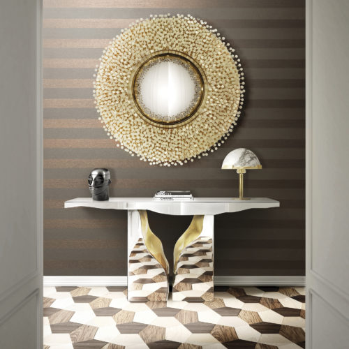 Picture of a chrome console that reflects the wooden inlay floor. Above it a round mirror with mother-of-pearl dots. Behind it horizontally installed Infinity striped wallcovering.