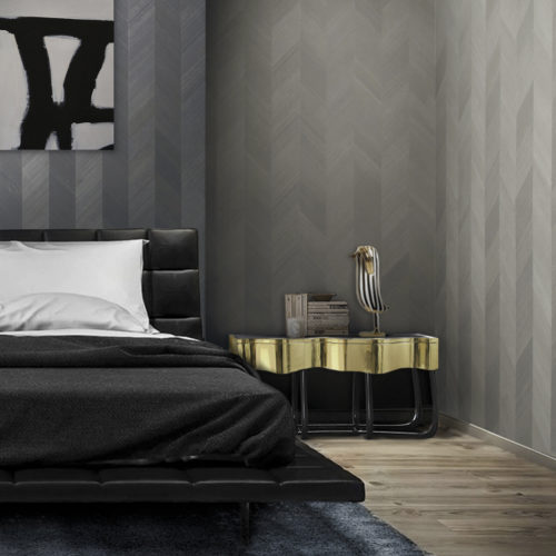 Bedroom with a black leather bed and golden nightstand. Abstrack black and white painting on the wall. Walls dressed in wood veneer wallcovering from the Omexco Infinity range.