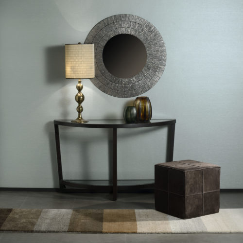 Peaceful decor with round mirror, leather poof and golden lamp. Behind it: light blue Infinity wallcoverings.