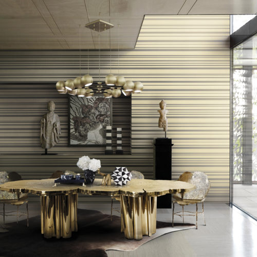 Golden dining table with wood structure in a well lit dining room. Golden striped Infinity wallcovering give the room extra depth. Artworks in black and white.