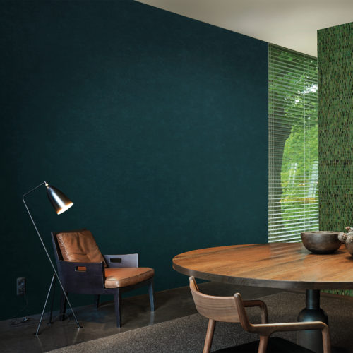 Living room with cosy leather chair and reading light. On the wall a deep green Kaleidoscope wallcovering.