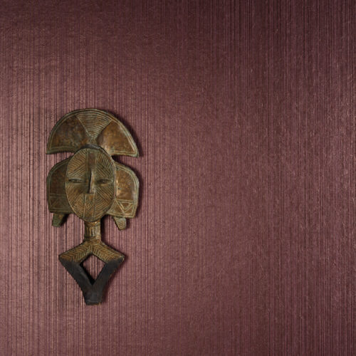 Wall with a bordeaux wallcovering, reflecting the light. A wooden african mask looks at us.