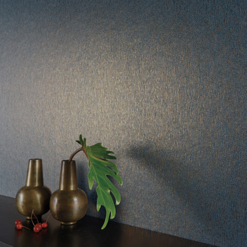 Impressive dark bleu wallcovering with golden foil delicate stripes. Two brown vases and cherries on a shelf.