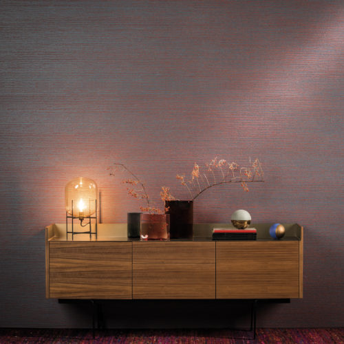 In this wallcovering in petrol and orange, the yarns consist of cute interlocking loops, as if crocheted. A wooden console houses a beautiful lamp and two gold and silver arty spheres.