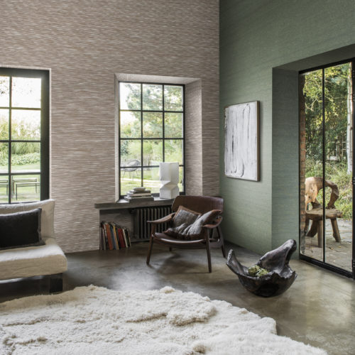 Grand interior picture with huge, soft animal skins on the floor. The wooden artworks give the interior an ethnic twist. On the wall: green and brown paper strips wallcovering from the Koyori range.