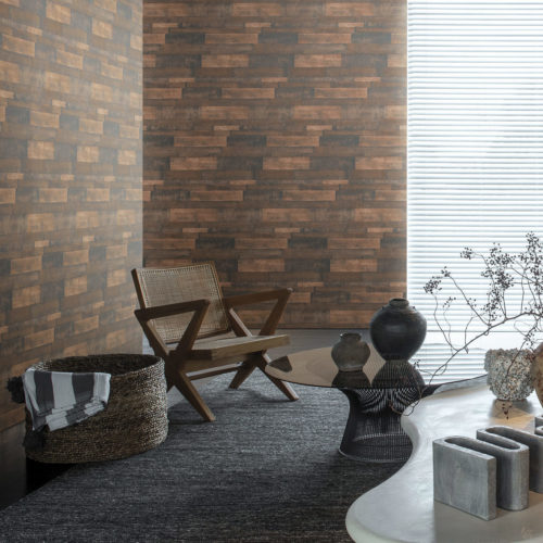 Impressive interior with ethnic details. On the walls: a horizontally installed wallcovering from our Loft collection. The walls look like oxidised metal. We see a wooden chair and woven basked.