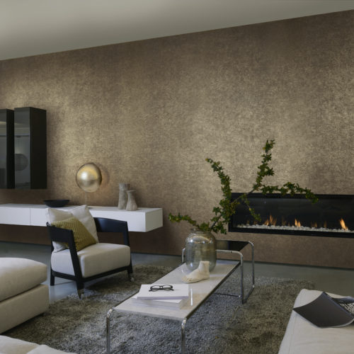 Tactile living room with contemporary fireplace. We see the white leather sofa, black and white consoles on the wall and outstanding golden sfere lamp. The wall is dressed in brown and gold wallcovering by Omexco.