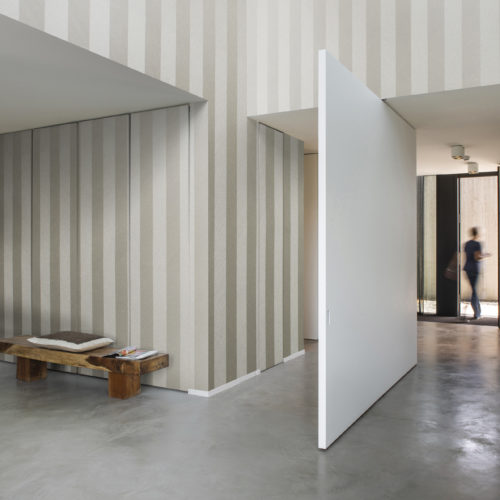 Contemporary hallway with pivoting white door. Behind the Omexco Portfolio wallcovering, cupboard doors are hiding.