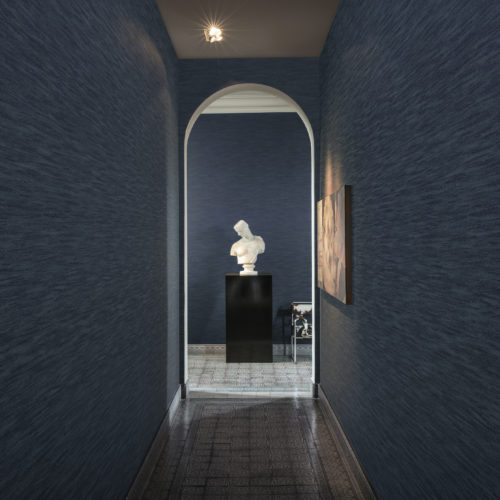 Narrow dark blue hallway looking out on a white buste and a chair with cow's skin. Floor with old tiles.