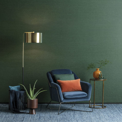 Decor with blue velvet chair, orange and green cushions and vases. Green Portfolio wallcovering on the wall.