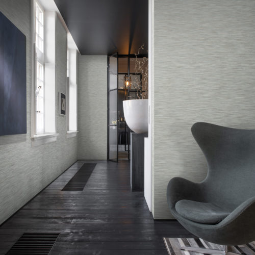 Room with black wooden floor and black iron door in the back. In the front a grey armchair. Classic Omexco wallcoverings on the wall.