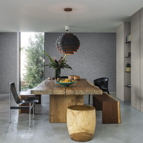Dining room with wooden table, wooden stool and different black chairs. Concrete floor. Horizontally installed wallcoverings on the walls.
