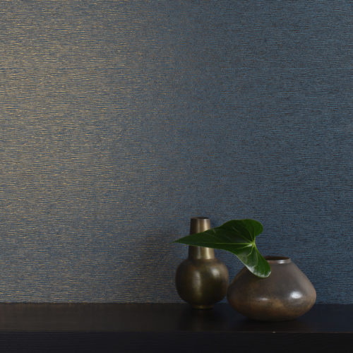 This elegant plain wallcovering from the Omexco Rainbows range exists in many colours. The little weavy foil line gives it a little extra. Shown in this picture with two bronze vases to bring out the bronze in the foil.