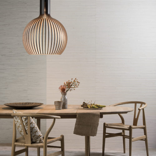 Natural look wooden table with two Wegner wishbone chairs. Perfect setting to Shades of Pale natural wallcoverings by Omexco.