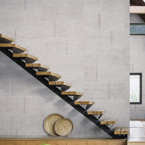 Wall with raffia blocks wallcovering. Stairs run diagonally through the picture.