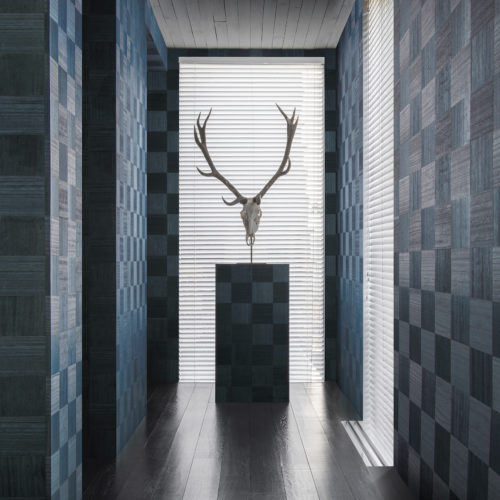 La collection Sycamore d'Omexco est uniquement définie par une célébration du bois naturel. Nos revêtements muraux élégants et raffinés donnent vie à cette matière noble et authentique. Nous voyons un couloir bien éclairé présentant le design bleu des 'échecs': des carrés de bois dans des directions différentes comme un échiquier.