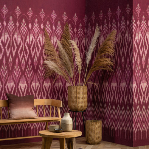 Tribu celebrates deeply authentic beauty as Omexco explores the art of weaving with paper. In this picture, we see the corner of a living room where the walls are decorated with a raspberry coloured ikat pattern.