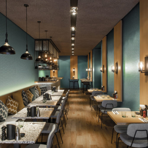 Restaurant with terazzo tables, a cosy sitting bench with pillows, bar in the back. Omexco Vogue teal wallcovering and wooden panels on the walls.