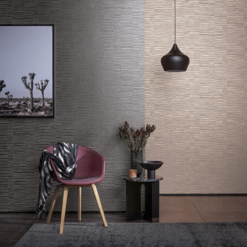 Decor with a burgundy chair, marble table with black vase and burgundy flowers, black pending lamp. On the wall a picture of cactusses and Vogue Omexco wallcoverings in tactile colours.