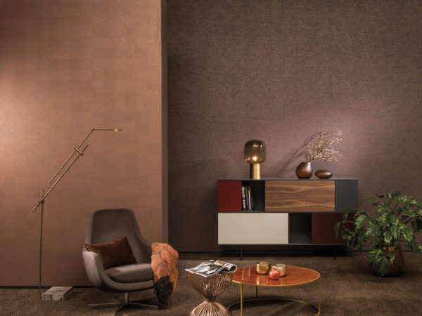 Cosy room in brown colours. Velvet ottoman with plaid. Against the far wall a sideboard with different drawers. Omexco Avenue wallcoverings on the walls.