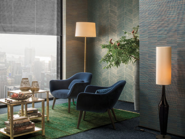 Contemporary interior with green and blue Avenue wallcoverings. Green rug, night blue velvet armchairs, golden coffee tables. Large window with city skyline.