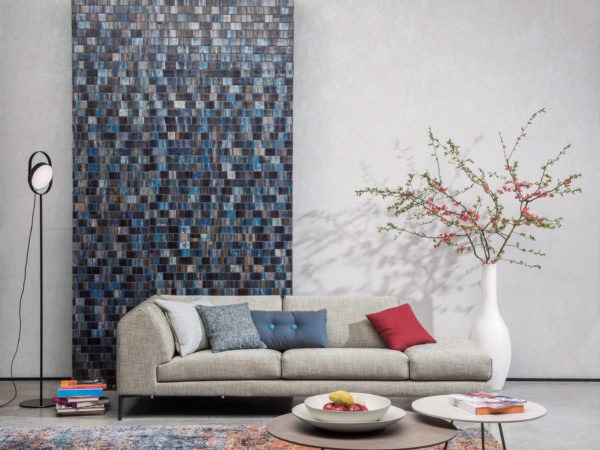 Well balanced decor with bakbak Borneo wallcovering, sofa with blue and red pillows. White vase with blossoming branches. Two round coffee tables. Carpet with red and blue hints.