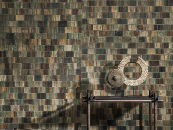 Detail of green and brown bakbak wallcovering. Rotan shelves with two round artworks.