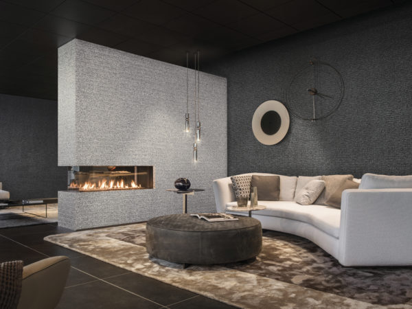 Impressive living room with slightly bent leather sofa. The living room is divided in two by a wall, adorned in capiz wallcoverings with capiz shells. On the other walls, the non-woven from the same collection.
