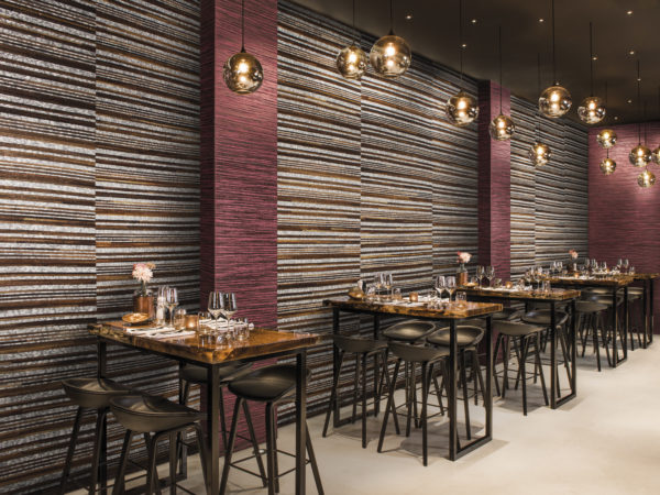 The Omexco wallcoverings are perfect for projects. This impressive restaurant combines two products from the Capiz range. The bordeaux zebrano stripe on non-woven and the capiz & wood combination. The high tables and stools are ready for a busy dinner service.